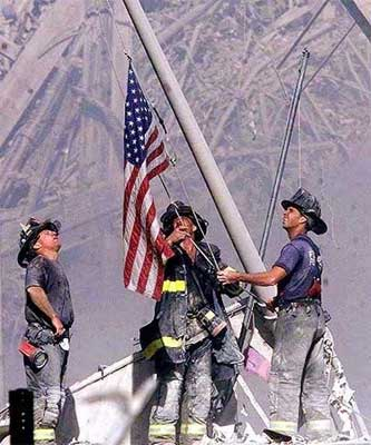 Firemen raising flag among Sept 11 rubble.